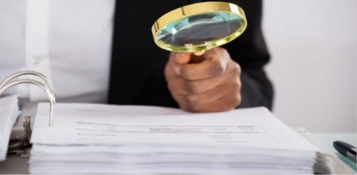 MAN READING A BOOK WITH MAGNIFYING GLASS