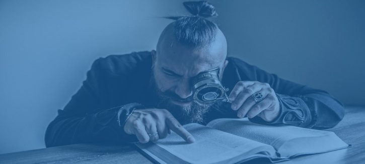 Man reading a book using a magnifying glass